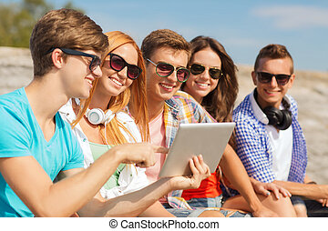 group of smiling friends with tablet pc outdoors -...