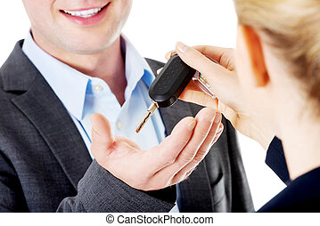 Car salesman handing over the keys for a new car to a young...