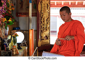 Young Buddhist Monk light incense sticks in Laos temple