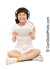 sitting little girl holding a tablet with earphone