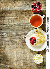 oat scones with cream cheese and caramelised plums on a dark...