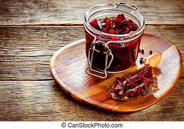 pickled beets in the jar on a dark wood background tinting...