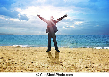 Relieved - A man standing on beach with open arms with...
