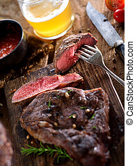 steak and beer - close up view on nice fresh steak on color...
