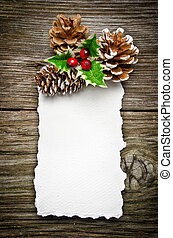 Christmas greeting card on wooden top, with holly and pine...