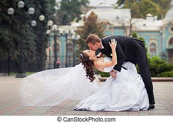 beautiful wedding couple - young handsome groom in black...