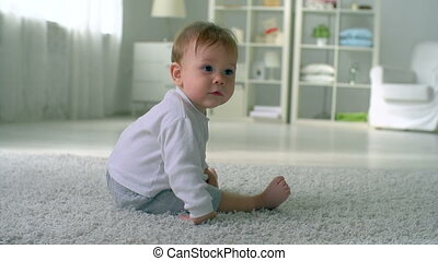 Playful Tot - Baby sitting on the floor and playing on his...