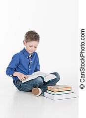 Cute boy reading book isolated on white. boy holding book...