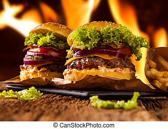 hamburger with fries on wooden table and fire background