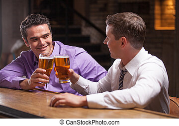 two young man talking at counter. two friends sitting in bar...