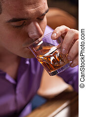 closeup of young man drinking alcohol drinks. man sitting in...