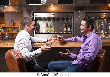 two young man talking at counter two friends sitting in bar...