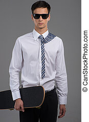 man wearing black glasses holding skateboard. handsome guy standing on grey background with tie