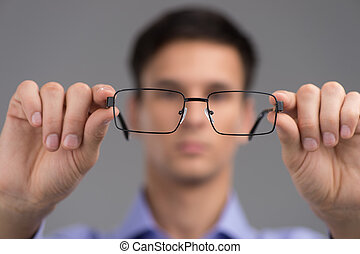 man wearing glasses to improve vision. man holding black...