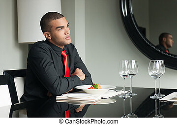 young man waiting in restaurant and thinking. guy sitting at...