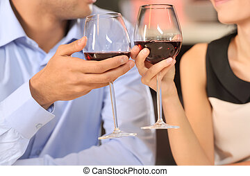 Two people toasting with wine glasses cropped image of...