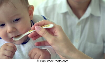 Infant Food - Unrecognizable mother and father feeding their...