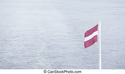 Flag of Latvia - On flagpoles waving Flag of Latvia