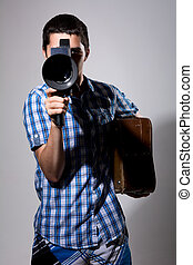 Young man filmmaker with old movie camera and a suitcase in...
