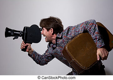 Portrait of a cameraman with old movie camera. Happy...