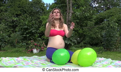 woman play balloon park - smiling pregnant woman play with...