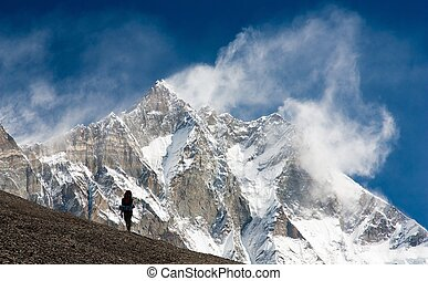 Lhotse with windstorm, turist and snow clouds - top of...