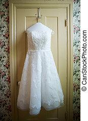 Wedding Dress - A wedding dress hanging from a door.