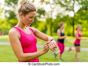 blond woman setting her timer before jogging - Portrait of...