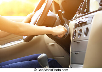 driver hand starting car engine - woman driver starting the...