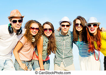 group of young people wearing sunglasses and hats hugging...