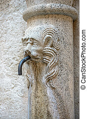 Drinking water source with stone lion head in medieval...