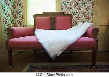 Wedding Dress on Sofa - a wedding dress spread on a read...