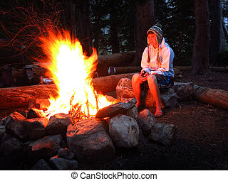 Girl Alone by Campfire While Camping - Woman looking at...