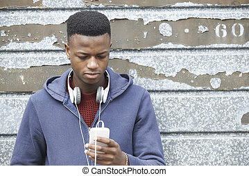 Teenage Boy Wearing Headphones And Listening To Music In...