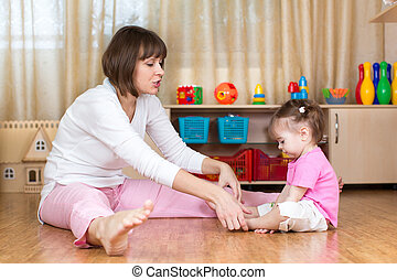 mom and her child kid doing gymnastic at home