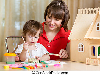 cute mother and her daughter kid making by hand