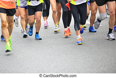 Unidentified marathon athletes legs running on city road