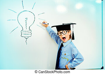 bright idea - Smart boy stands by the whiteboard in a...