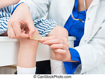Doctor puts adhesive bandage on child knee