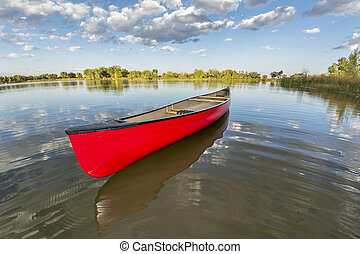 red canoe on a calm lake in a fisheye perspective, late...