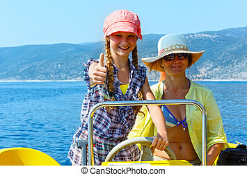 Mother with daughter in a motorboat.