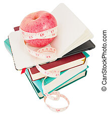 Big ripe red apple with white measure tape around it on pile...