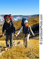Two hikers climbing up the mountain