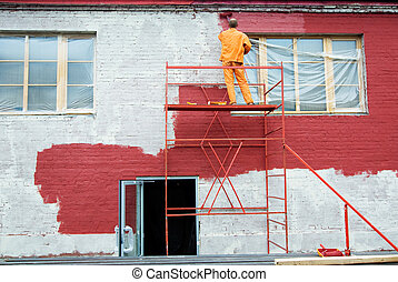 Painting in red - Man painting a brick wall in red