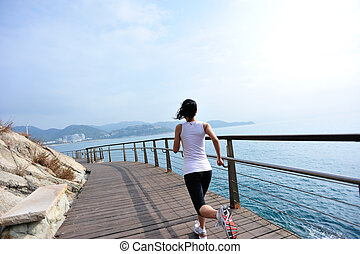 woman running on wooden boardwalk - healthy lifestyle sports...