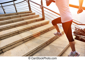 woman running on seaside stairs - sports woman running on...