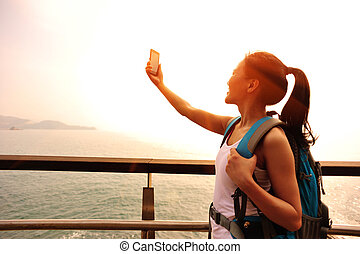 woman hiker taking self photo on sunrise seaside