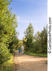 Grandfather and grandchild walking outdoors - Back view of...