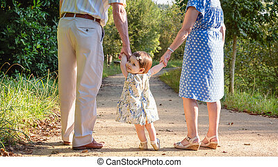 Baby granddaughter walking with her grandparents outdoors -...