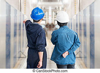 A team of construction workers with helmets at work place in...